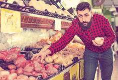 Young male seller offering potatoes. Glad cheerful positive male seller offering potatoes in grocery shop Royalty Free Stock Photo