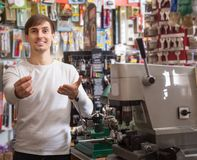 Young male seller posing with key. Young positive male seller posing with key at tooling section of household store Stock Image