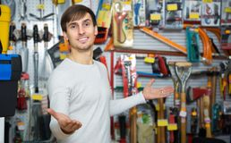 Young male seller posing at tooling section. Positive young male seller posing at tooling section of household shop Stock Photo