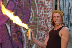 Young male setting spray on fire and sticking his tongue out Stock Photo