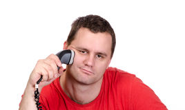 Young male shaving with electric shaver royalty free stock photography