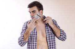 Young male shaving with razor blade Stock Image
