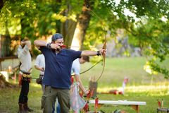 Young male shooting a bow on an annual Medieval Festival, held in Trakai Peninsular Castle stock photography
