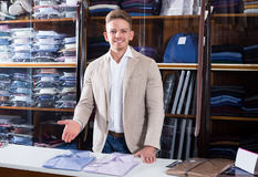 Young male shopping assistant offering shirts. Young male shopping assistant offering various shirts in men's cloths store Stock Image
