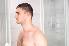 Young male after shower standing in the bathroom Royalty Free Stock Image