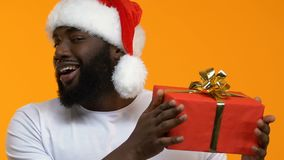 Young male showing gift box and winking camera, seasonal discount, celebration. Stock footage stock footage