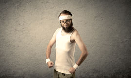 Young male showing muscles. A young man with beard, headstrap and glasses posing in front of blank grey wall background, imagining he has big muscles Stock Photo