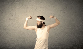 Young male showing muscles. A young man with beard, headstrap and glasses posing in front of blank grey wall background, imagining he has big muscles Royalty Free Stock Photography
