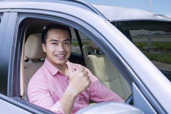 Young male showing thumb up in car Royalty Free Stock Photo