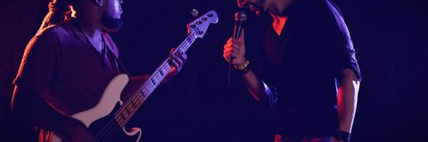 Male singer with guitarist performing at music concert. Young male singer with guitarist performing at music concert Royalty Free Stock Photos
