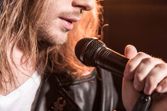 Young male singer with microphone on stage. Cropped shot of young male singer with microphone on stage Royalty Free Stock Photo
