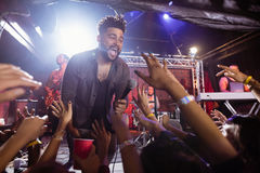 Young male singer performing on stage by crowd at nightclub. During music festival Royalty Free Stock Photo