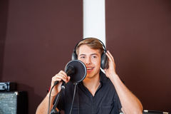 Young Male Singer Performing In Studio. Happy young male singer performing in recording studio Royalty Free Stock Images