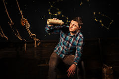 A young male sits on a chest, looking into glass bottle and tryi Royalty Free Stock Images