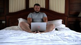 Young male sitting on bed and working on laptop. 4k. stock footage