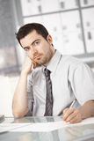 Young male sitting at desk writing notes thinking. Young businessman working in bright office, sitting at desk, writing notes, thinking Stock Photo