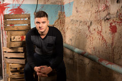 Young male sitting on empty packing crates in terrible basement Royalty Free Stock Photos