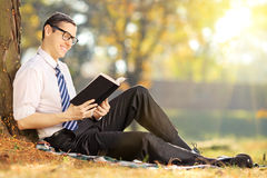 Young male sitting on green grass and reading book in park Royalty Free Stock Photos
