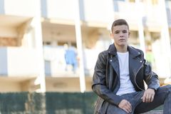 Stylish young man in leather jacket looking at camera, sitting i royalty free stock images
