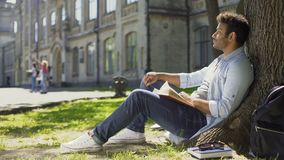 Young male sitting under tree with book looking around, having pleasant thoughts