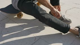A young male skateboarder ties a lace and then leaves on a skateboard