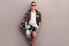 Young male skater holding a skateboard. And leaning against a gray wall Stock Images