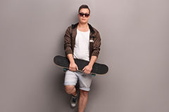 Young male skater holding a skateboard. And leaning against a gray wall Royalty Free Stock Photos
