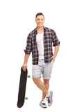 Young male skater leaning on his skateboard Royalty Free Stock Images