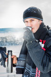 Young male skier drink outdoor. Young male skier drink beverage outdoor in winter forest Stock Images