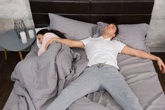 Young male sleeping in free fall position with his girlfriend oc. Cupied the whole bed, wearing pajamas, near bedside table with candles Royalty Free Stock Image