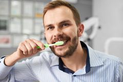 Young male is smilig to the camera while cleaning his teeth with a tooth brush in a modern dental office. Young attractive male is smilig to the camera while Stock Image