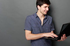 Young male smiling using laptop computer. Against gray background Stock Photo