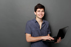 Young male smiling using laptop computer. Against gray background Royalty Free Stock Photography