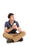 Young male smiling using mobile phone and looking up Stock Photo