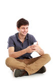 Young male smiling using mobile phone Royalty Free Stock Photos