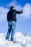 Young male on snow taking picture with smartphone Royalty Free Stock Photos