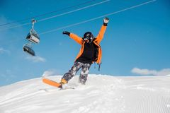 Young male snowboarder in colorful sportswear riding with snowboard. From snow hill on the background of cable cars Stock Photos