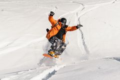 Young male snowboarder in orange sportswear jumping on the snow slope. Young male snowboarder in the orange sportswear jumping on the powder snow slope with his Stock Photos