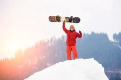 Young male snowboarder standing on the top of the snowy hill with, holding snowboard in hand above head. Smiling to the camera, showing thumbs up. Mountains Royalty Free Stock Photography