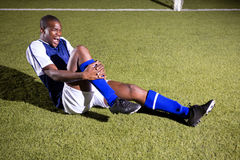 Young male soccer player shouting in agony with knee pain Stock Image