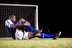 Young male soccer player suffering from knee pain on playing field Stock Photo
