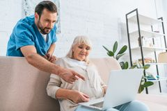 Young male social worker pointing with finger at laptop white senior woman. Sitting on couch royalty free stock photo