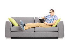 Young male on a sofa reading a book. Isolated on white background Royalty Free Stock Photo