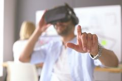 Young male software programmer testing a new app with 3d virtual reality glasses in office. royalty free stock photos