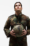 Young male soldier holding helmet Royalty Free Stock Images