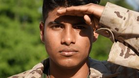 Young Male Soldier Saluting. A young hispanic male teen Stock Photos