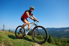 Young male sportsman cyclist in helmet, sunglasses and full equipment riding bike on grassy hill. Mountains and blue summer sky on background. Active lifestyle Royalty Free Stock Photo