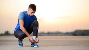 Young Male Sportsman Tying Running Shoes and Preparing for Urban Run at Sunset. Healthy Lifestyle and Sport Concept. royalty free stock images