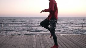 Young male sportsman warming up near the sea. Exercising, training outdoors. Side view of man exercising raising his