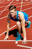 Young male sprinter in starting blocks. Young male athlete is all set for the big race Stock Image